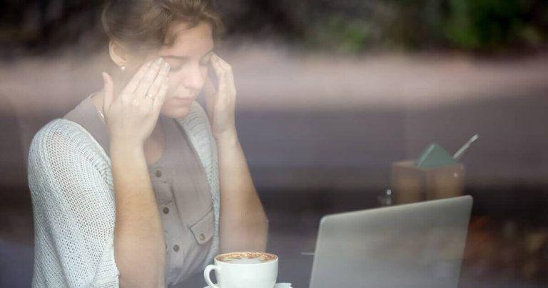 Frau gestresst im Job vor Laptop
